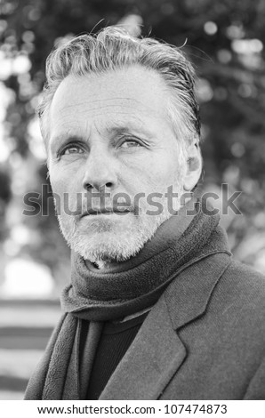 pensive looking mature man with beard wearing a scarf and jacket. - stock photo