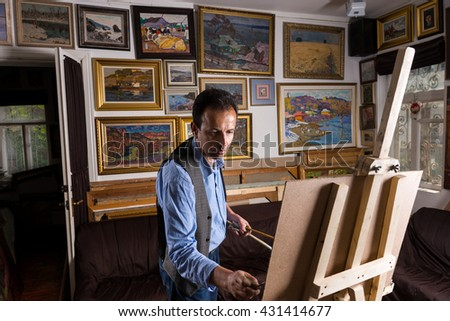 Pensive male artist ending his masterpiece holding  paintbrushes and rag in his hands in a gallery with background of original artworks hanging on the wall - stock photo