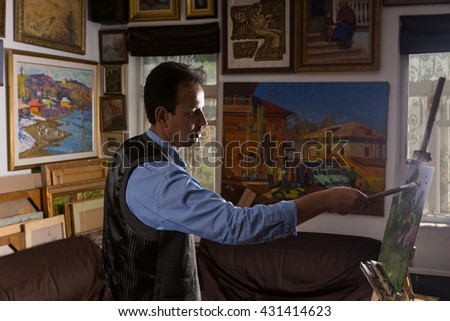 Pensive male painter putting finishing strokes in a gallery with background of original artworks hanging on the wall - stock photo