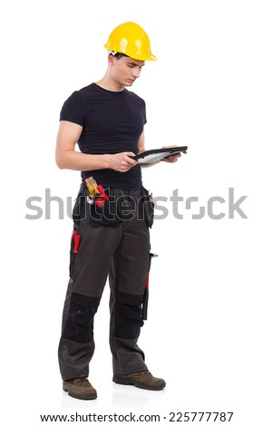 Pensive manual worker using a digital tablet. Full length studio shot isolated on white. - stock photo