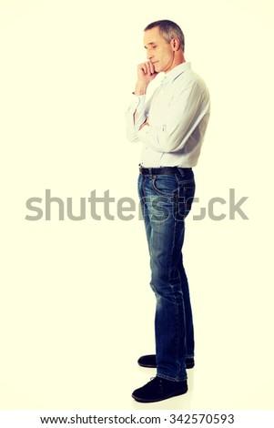 Pensive mature man touching chin. - stock photo