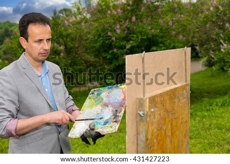 Pensive middle-aged artist holding a palette standing in front of a sketchbook during an art class in a forest - stock photo