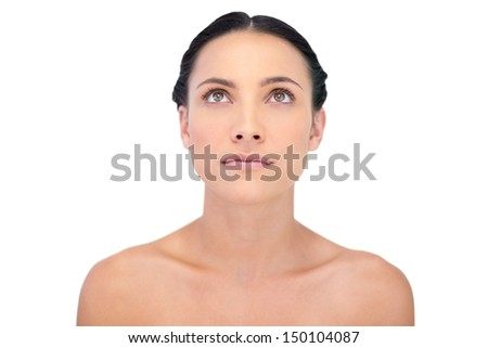 Pensive natural model posing looking up on white background - stock photo