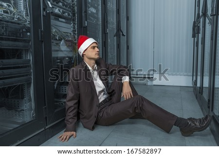 pensive network Engineer  in the server in Santa Claus lying on the floor on colorize background - stock photo