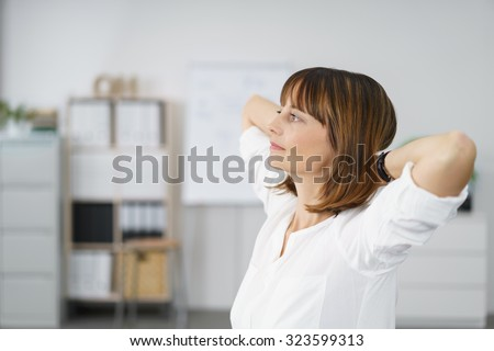 Pensive Office Woman with Hands Behind her Head and Looking to the Left of the Frame. - stock photo