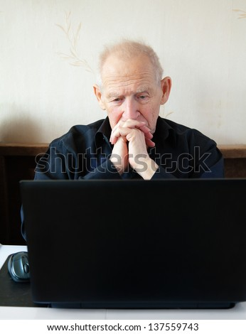 pensive old man in front of the laptop - working and thinking - stock photo