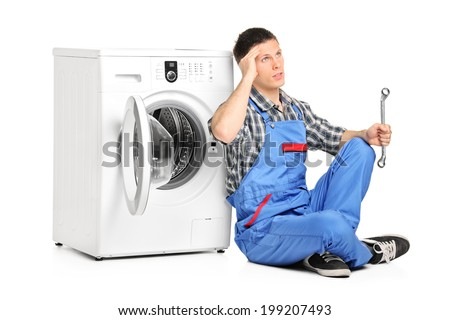 Pensive plumber fixing a washing machine isolated on white background - stock photo