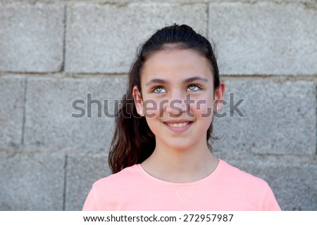 Pensive preteen girl with blue eyes outside thinking - stock photo