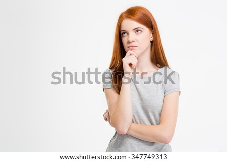 Pensive pretty young redhead woman with long hair thinking and dreaming over white background - stock photo