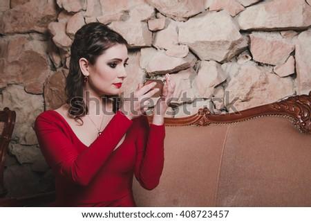 Pensive sad woman in red dress holding a mirror, thoughtfully looks at her face with bright makeup smoky eyes, red lips, hairstyle. Elegant portrait brunette 30 year old female in classic interior. - stock photo