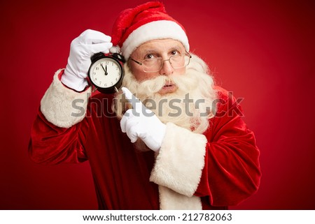 Pensive Santa Claus pointing at clock showing five minutes to midnight - stock photo