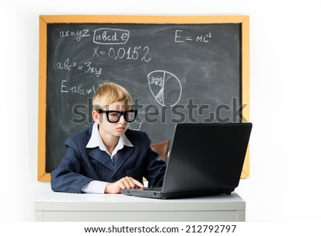 Pensive schoolboy sits at the notebook - stock photo