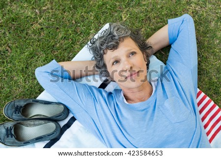 Pensive senior woman lying on towel on grass. High angle view of thoughtful mature woman thinking. Retired woman contemplating her life after retirement. - stock photo