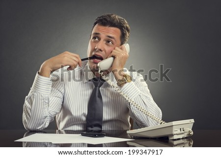Pensive serious entrepreneur looking up and biting a pen while listening to clever business advice on phone. Mindful businessman thinking and making research for smart business solution on phone. - stock photo
