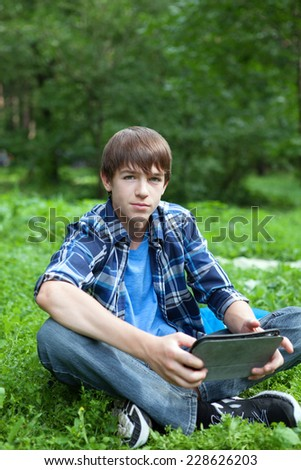 pensive, serious teenager sitting on grass in park with tablet, outdoor, schoolboy - stock photo