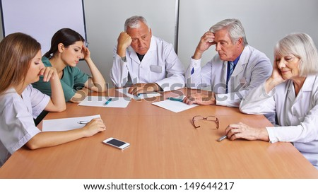 Pensive team of doctors and nurses in a meeting - stock photo