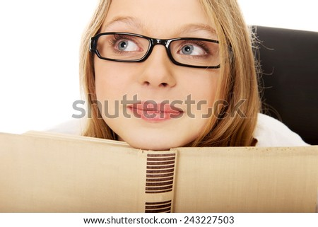 Pensive teenage woman with a book - stock photo