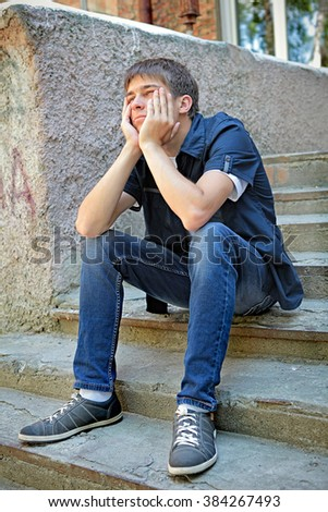 Pensive Teenager sit on the City Street - stock photo