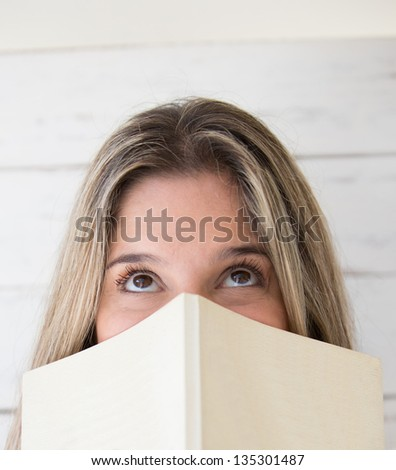 Pensive woman holding a book and looking up - stock photo