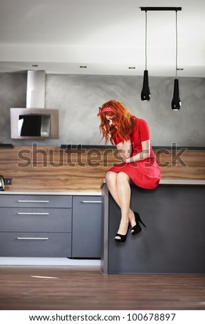 Pensive woman in a kitchen - stock photo