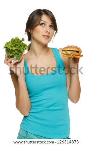 Pensive woman making decision between healthy salad and fast food, over white background - stock photo