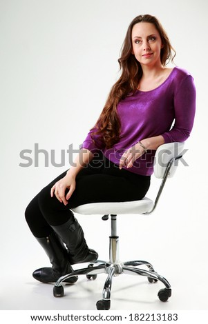 Pensive woman sitting on the chair over gray background - stock photo