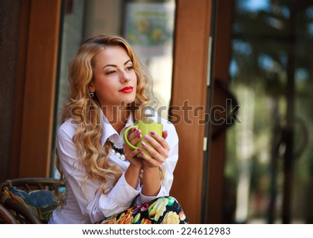 Pensive woman sitting with coffee cup and has a rest in spring cafe outdoors and dreaming looking far away - stock photo