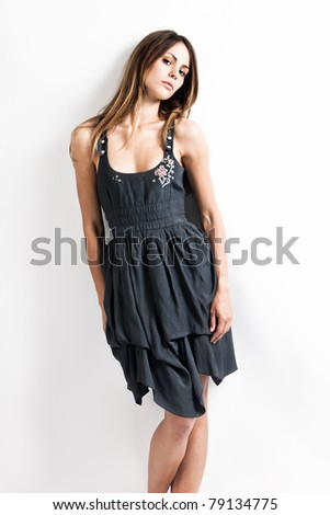 pensive young brunette woman in summer dress, studio shot - stock photo