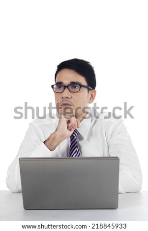 Pensive young businessman looking up with concentration - stock photo