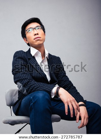Pensive young businessman sitting on the chair over gray background and looking up  - stock photo