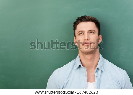 Pensive young man in a deep reverie standing against a green background staring thoughtfully into the air as he mulls over a problem - stock photo