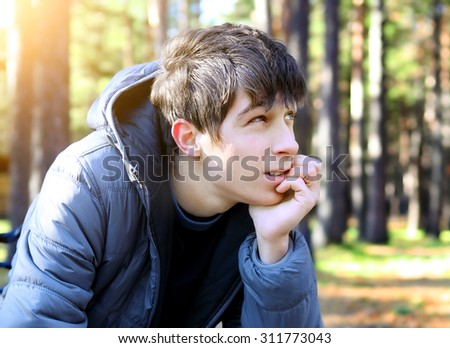 Pensive Young Man in the Autumn Park - stock photo