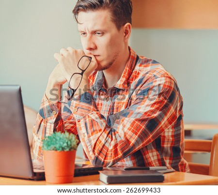 Pensive young man looking on laptop in the office - stock photo