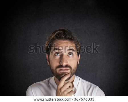 Pensive young man looks up at copy space - stock photo