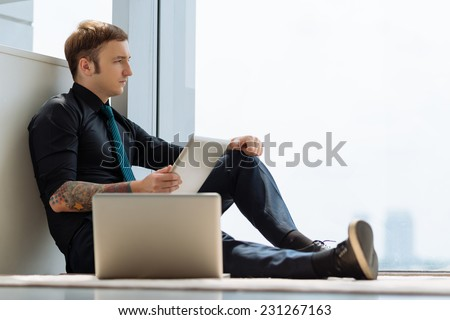 Pensive young man with laptop and digital tablet sitting by the window - stock photo