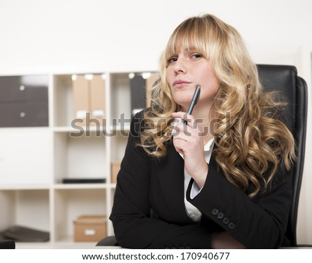 Pensive young manageress in the office sitting with her pen to her cheek staring off into the distance with a contemplative look - stock photo