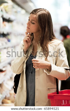 Pensive young woman at supermarket - stock photo