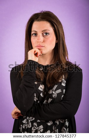 Pensive Young Woman on Violet Background - stock photo
