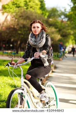 Pensive young woman riding a bicycle in the green city park - stock photo