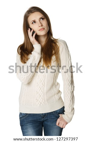 Pensive young woman talking on cell phone looking up, over white background - stock photo