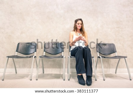Pensive young woman with mobile smart phone sitting in waiting room - Anxious female person using smartphone in hospital anteroom looking forward for exam test result - Neutral desaturated color tones - stock photo