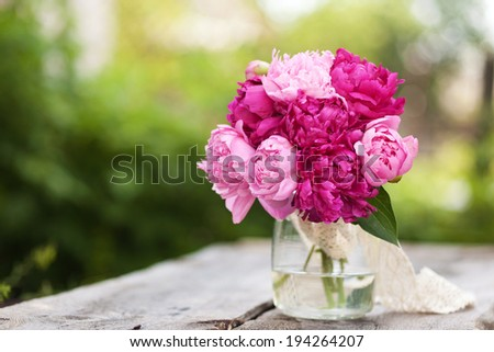 Peonies flowers in glass vase outdoor - stock photo