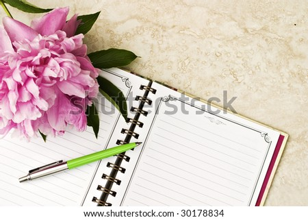 Peony on note book with ink pen - stock photo