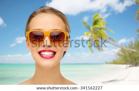people, accessory, summer vacation, travel and fashion concept - smiling young woman in sunglasses with pink lipstick on lips over tropical beach with palm background - stock photo