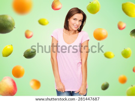 people, advertisement, diet, food and healthy eating concept - happy woman in blank pink t-shirt over fruits on green background - stock photo