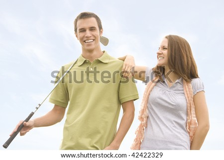 People against blue sky with golf clubs - stock photo
