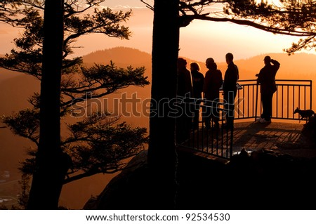People and a dog are watching this stunning sunset from a mountain overlook with trees silhouetted as are the people. - stock photo