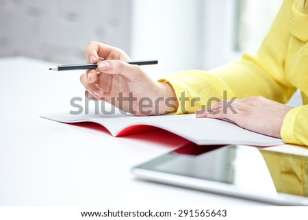 people and education concept - close up of female hands writing to notebook at school - stock photo