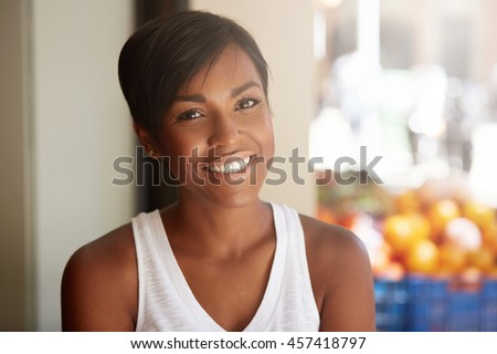 People and happiness concept. Cheerful African American young female with short haircut wearing white top, looking at the camera with happy smile. Human face expressions, emotions and feelings - stock photo