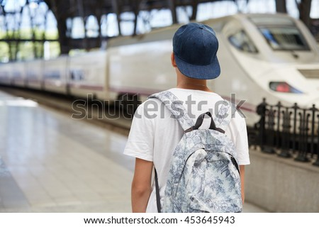 People and lifestyle concept. Back view of Caucasian high school student with backpack, wearing cap backwards walking alone against urban background with copy space for your advertising content - stock photo